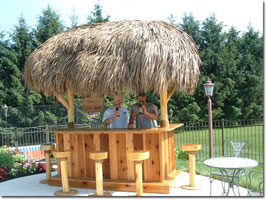 A beautiful tiki bar siting beside a pool on a sunny day.